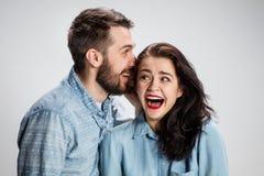 Jeune homme chuchotant à la femme un secret Photos libres de droits