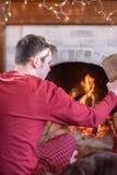 Jeune homme commençant le feu en cheminée le matin d'hiver image stock