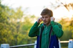 Jeune homme commun marchant dans la ville écoutant la musique avec des écouteurs de dans-oreille au coucher du soleil Thème de mu Image libre de droits