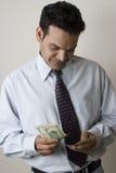 Jeune homme comptant l'argent Image libre de droits