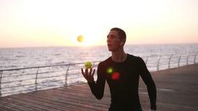 Jeune homme concentré avec les écouteurs sans fil blancs améliorant sa réaction - jonglant dans l'action, fin  Jeune homme banque de vidéos