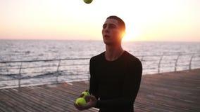 Jeune homme concentré avec les écouteurs sans fil blancs améliorant sa réaction - jonglant dans l'action, fin  Jeune homme clips vidéos