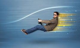 Jeune homme conduisant dans la voiture rapide imaginaire avec les lignes brouillées Photos stock