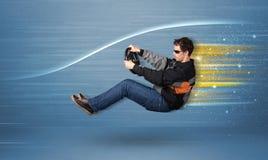 Jeune homme conduisant dans la voiture rapide imaginaire avec les lignes brouillées Photo stock