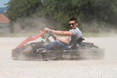 Jeune homme conduisant la course de Karting de kart images libres de droits