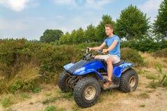 Jeune homme conduisant le quadruple en nature Image stock