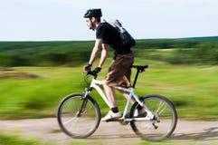 Jeune homme conduisant un vélo de montagne Image libre de droits