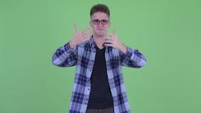 Jeune homme confus de hippie choisissant entre les pouces et les pouces vers le bas banque de vidéos