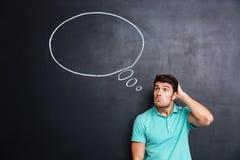 Jeune homme confus réfléchi se tenant et pensant au-dessus du fond de tableau noir images stock