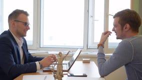 Jeune homme consultant l'avocat professionnel dans le bureau, fond rétro-éclairé banque de vidéos