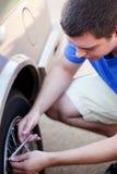 Jeune homme contrôlant la pression de pneu Photographie stock libre de droits
