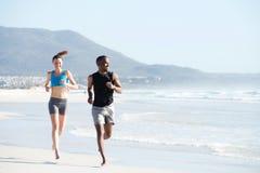 Jeune homme convenable et femme courant le long de la plage Image libre de droits