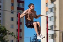 Jeune homme convenable faisant des pousées sur la barre horizontale dehors avec le grand effort Photo stock