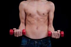 Jeune homme convenable s'exerçant avec l'haltère rouge Images stock