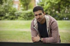 Jeune homme convenable se penchant sur le banc en parc Image libre de droits