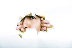Jeune homme coréen regardant par le trou de papier déchiré photographie stock