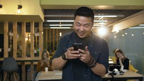 Jeune homme coréen utilisant le téléphone intelligent sur le fond moderne de bureau banque de vidéos