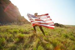 Jeune homme courant avec le drapeau des Etats-Unis Photos stock