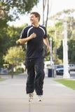 Jeune homme courant sur la rue Photo stock