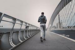 Jeune homme courant sur le pont moderne dans la ville Images libres de droits