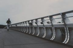 Jeune homme courant sur le pont moderne dans la ville photo libre de droits