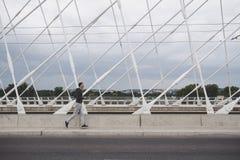 Jeune homme courant sur le pont moderne dans la ville, musique de écoute sur le smartphone photos libres de droits