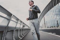 Jeune homme courant sur le pont moderne dans la ville, musique de écoute sur le smartphone Photographie stock libre de droits