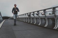 Jeune homme courant sur le pont moderne dans la ville, musique de écoute sur le smartphone Image stock