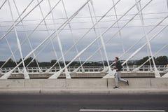 Jeune homme courant sur le pont moderne dans la ville, musique de écoute sur le smartphone Photo stock
