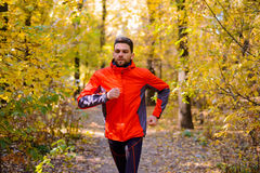Jeune homme courant sur Sunny Trail dans bel Autumn Oak Forest Image stock