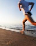 Jeune homme courant sur une plage au lever de soleil Effet de tache floue de mouvement photo libre de droits
