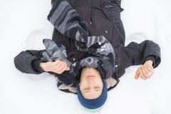 Jeune homme couvert dans la neige se trouvant au sol en chutes de neige z images libres de droits