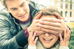 Jeune homme couvrant les yeux d'une amie étonnée heureuse Photo stock