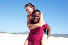 Jeune homme couvrant sa amie à la plage Photographie stock