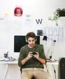 Jeune homme créatif de concepteur au téléphone fonctionnant au bureau et à la musique de écoute. image stock