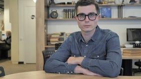 Jeune homme créatif en verres au travail regardant la caméra banque de vidéos