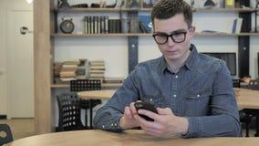 Jeune homme créatif en verres passant en revue l'Internet et employant Smartphone banque de vidéos