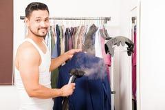 Jeune homme cuisant une chemise à la vapeur dans son vestiaire photographie stock