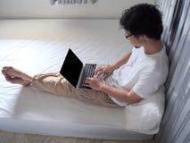 Jeune homme décontracté à l'aide de l'ordinateur portable d'ordinateur sur le lit dans la chambre à coucher Internet de concept d photo stock