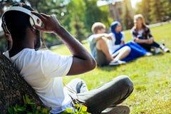 Jeune homme décontracté écoutant la musique dehors photographie stock libre de droits