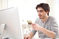 Jeune homme décontracté payant en ligne avec sa carte de crédit Photo stock