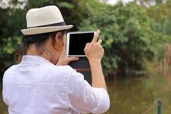Jeune homme décontracté prenant une photo contre le comprimé à l'arrière-plan extérieur photos stock