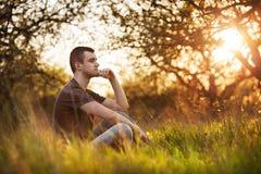 Jeune homme décontracté s'asseyant dans l'herbe Photos libres de droits