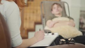 Jeune homme décontracté s'asseyant sur un berceau dans le bureau d'un psychologue, lui indiquant au sujet de ses problèmes tenant banque de vidéos