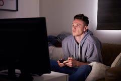 Jeune homme dépendant au jeu visuel à la maison images stock