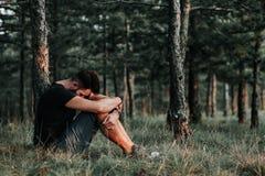 Jeune homme déprimé seul s'asseyant dans les bois images stock