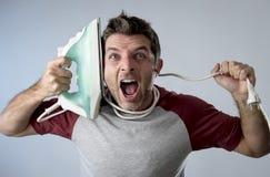 Jeune homme désespéré et frustrant fol faisant les travaux domestiques tenant le fer Image libre de droits