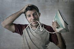 Jeune homme désespéré et frustrant fol faisant les travaux domestiques tenant le fer et le câble dans la bouche Image libre de droits