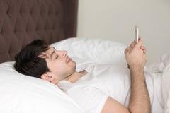 Jeune homme détendant dans le lit à la maison utilisant le smartphone mobile photos libres de droits