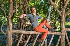 Jeune homme détendant dehors par des arbres Photo libre de droits